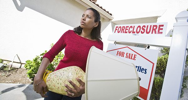 woman standing next to foreclosure sign