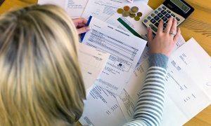 woman computing her bills using calculator